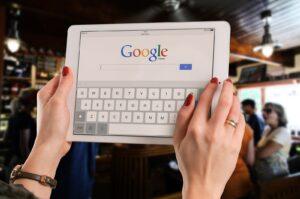 Mulher segurando um tablet com o campo de busca da Google)