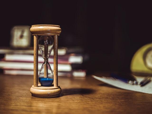 Ampulheta marrom com areia azul em sua base em cima de uma mesa com livros no fundo