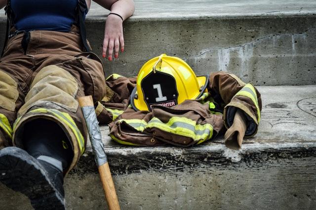 Uniforme do corpo de bombeiros, com o chapéu amarelo e uma pessoa sentada ao lado