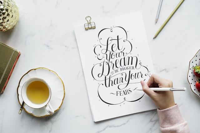 """Pessoa escrevendo em uma folha com a frase """"Let your dreams be bigger than your fears"""" e uma xícara de chá ao lado"""